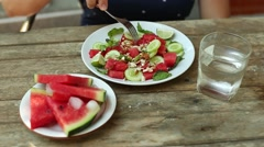 Woman eating salad with watermelon and cucumber - stock footage