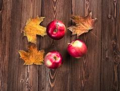 Autumn border from apples and fallen leaves - stock photo