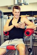 Smiling young man with smartphone in gym Kuvituskuvat