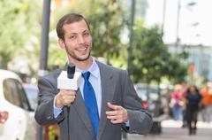 Attractive professional male news reporter wearing grey suit holding microphone - stock photo