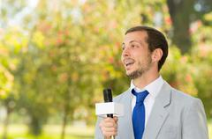 Successful handsome male news reporter wearing light grey suit working outdoors - stock photo