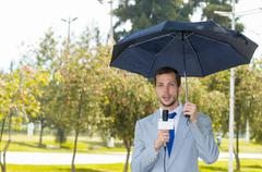 Successful handsome male journalist wearing light grey suit working in rainy - stock photo