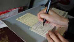 Tourist hand filling custom immigration form before landing Stock Footage
