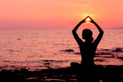 Woman silhouette sitting in lotus position on sea background back lit Stock Photos