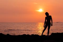 Standing woman silhouette on sea background back lit Stock Photos