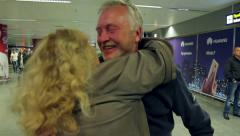 Wife meets her husband at the airport with flowers. Hugs of two loving people. Stock Footage