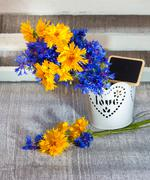 wild flowers blue and yellow colors  in a decorative vase with tablet for tex - stock photo