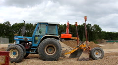 Blue tractor passing excavator doing construction work Stock Footage
