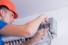 Air conditioning master preparing to install new air conditioner. Stock Photos