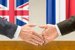 Representatives of the UK and France shake hands - stock photo