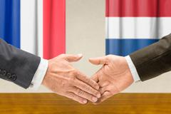 Representatives of France and the Netherlands shake hands - stock photo