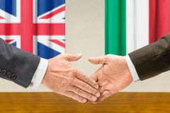 Representatives of the UK and Italy shake hands - stock photo
