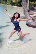 cheerful woman jumps at sea level - stock photo