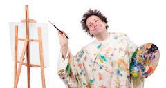 Happy painter paints on canvas Stock Photos