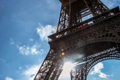Sun shines through construction Eiffel Tower Stock Photos