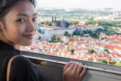 Stock Photo of Woman watches cityscape of Prague from outlook tower