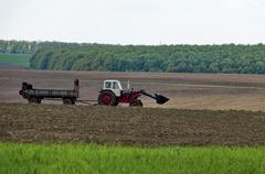 Wheeled tractor distribute manure over a field - stock photo