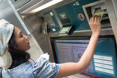 Young woman buys a ticket vending machine - stock photo