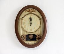 clock with pendulum hanging at the wall - stock photo