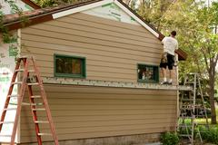 Stock Photo of Installing cementboard siding