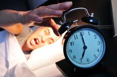 Young man in bed stopping the alarm clock Stock Photos