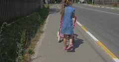 A Little Girl drives a baby carriage - stock footage