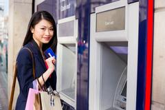 young chinese girl at the cashpoint - stock photo
