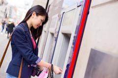 Young chinese woman withdrawing money at the cashpoint Stock Photos