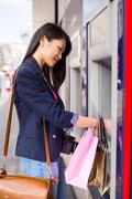 young chinese girl withdrawing money at the cash point - stock photo