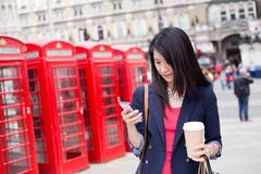Chinese girl in london checking her phone with a coffee Stock Photos