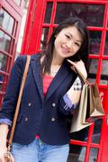 young chinese girl showing a phone me symbol by a london phonebox - stock photo