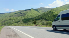 White van traveling at speed on the roads against the backdrop of mountains and Stock Footage