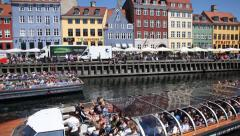 Tourist boats sail in old town Nyhavn,  a 17th century waterfront pier harbor Stock Footage