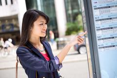 young chinese tourist checking the bus time table - stock photo