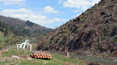 Tree stumps after deforestation located on the hill near the river in the Stock Footage