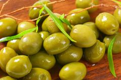 Fresh green olives on cutting board - stock photo