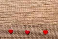 Red hearts on abstract cloth background Stock Photos