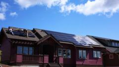 Stock Video Footage of BUILDERS INSTALL SOLAR PANELS ON ZERO NET ENERGY HOME
