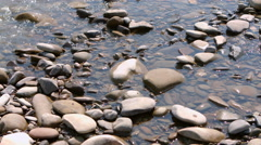 Sea pebbles in water. Ripples on the surface of water and solar patches of light Stock Footage