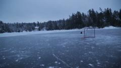 Stock Video Footage of Frozen lake pan up to hockey net