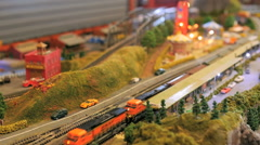 A model toy train passes a town with a carnival in a railroad set Stock Footage