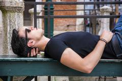 Stock Photo of Attractive young man laying down on wood bench