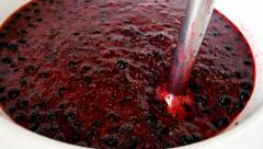Woman makes jam with blackcurrants Stock Footage