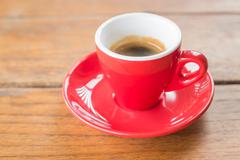 Fresh brewed hot espresso in red cup - stock photo