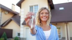Happy girl with keys next to her new house - stock footage