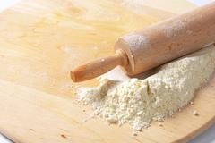 Flour and rolling pin on a wooden board - stock photo