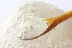 Pile of finely ground flour and wooden spoon Stock Photos