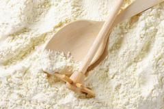 Finely ground flour, wooden beater and spoon Stock Photos