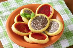 Mini tarts with jam and chocolate coconut filling - stock photo