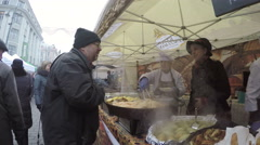Man buy freshly cooked baked food from outdoor tent stall Stock Footage